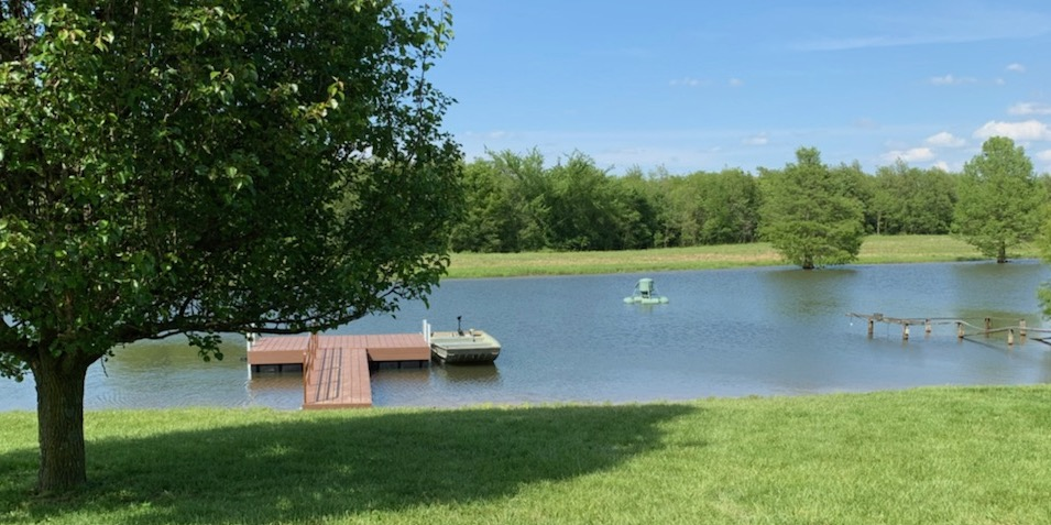 Pond with dock, boat and floating fish feeder